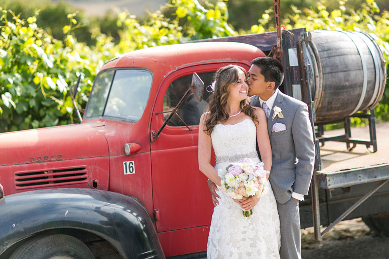Peacock Farms Wedding Bride and Groom Bride and Groom holding each other in front of a red vintage truck (1 of 2)