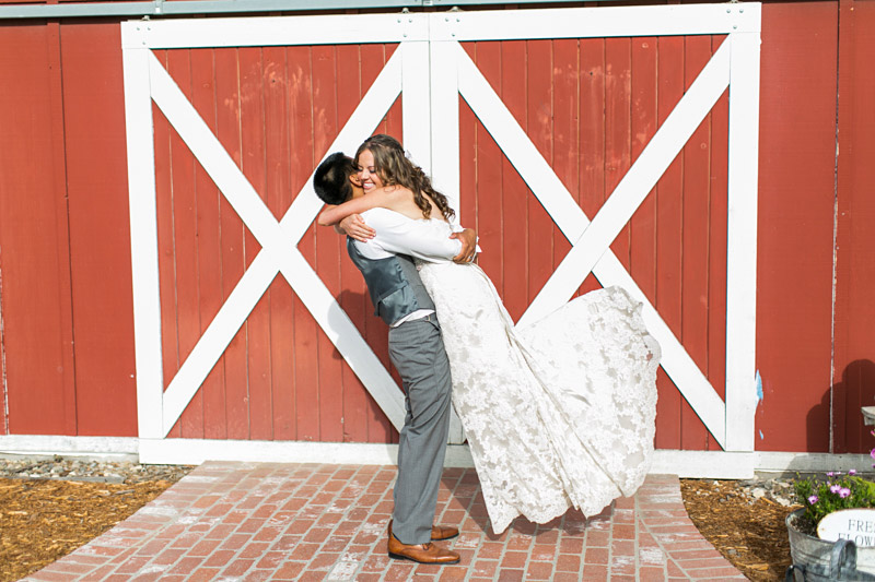 Peacock Farms Wedding Groom lifting Bride in front of a red barn
