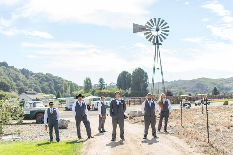 Greengate Ranch Wedding Groomsmen in the field under the windmill