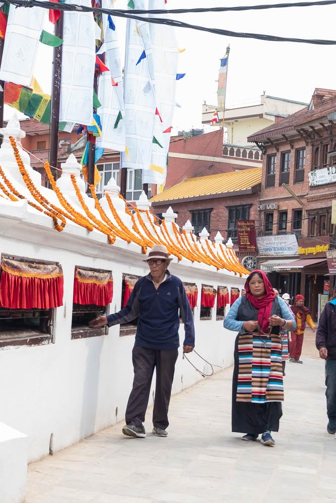 Buddhist faithful practicing pradakhshina (circumnabulation)around the Boudhanath Stupa, Kathmandu, Nepal.