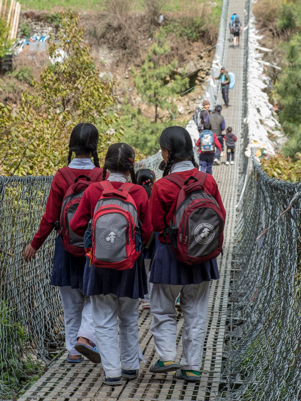Young girls crossing to Dudh Kohsi on their way to school, Phakding, Nepal.