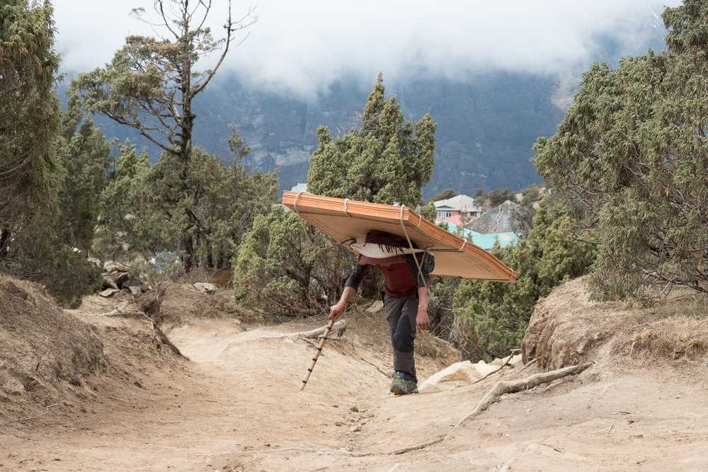 Porters carry goods and materials from helicopter drop to to town in the road-less region of Khumbu Nepal.