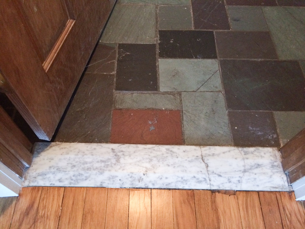Wood floor from the adjoining room transitions to flagstone via this cracked marble threshold.