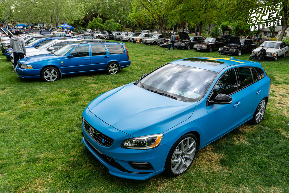 "A Volvo V60 Polestar, in Polestar Blue, with a clear matte vinyl wrap on top. As you can see, the park was divided up by model with a row of ""R"" cars followed by a row of 240s."