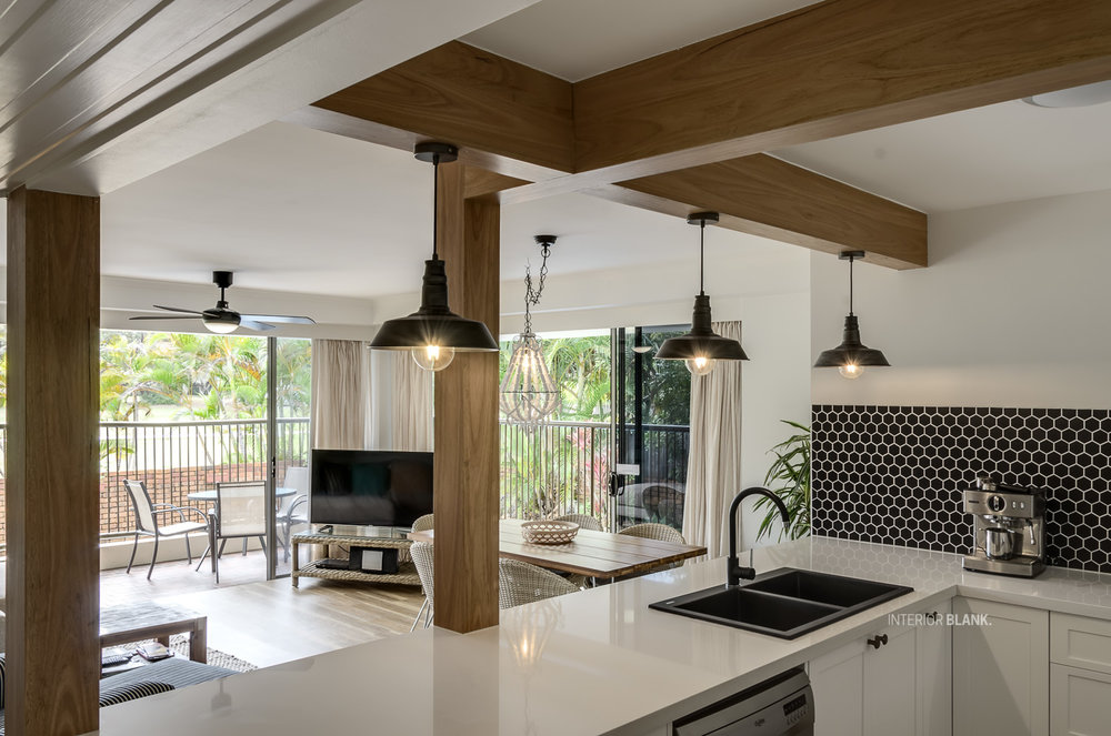 Kitchen design Byron Bay for AIRBNB beachfront apartment. Designed By Interior Blank. Timber posts, white stone tops. Black Pendant lights