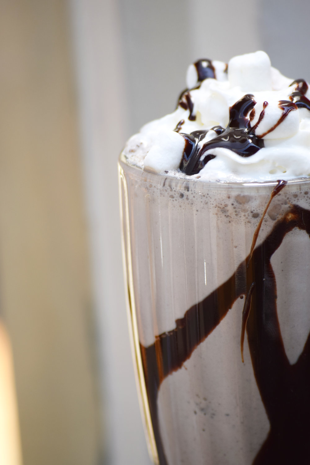 A chocolate milk shake zoomed in with marshmallows and whipped cream