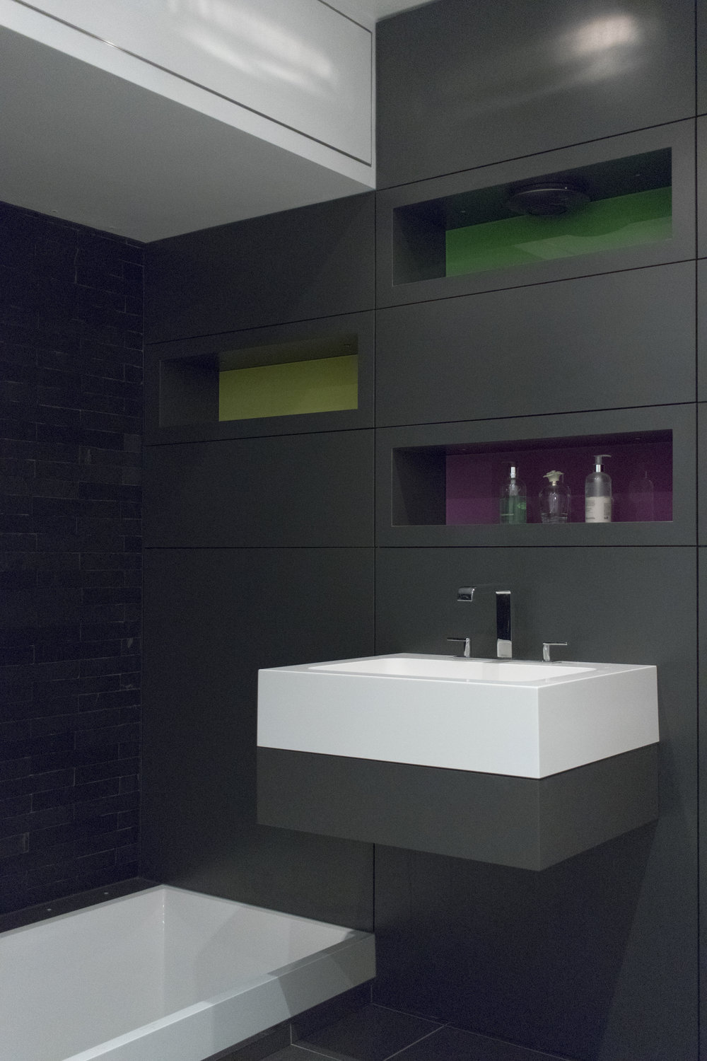 Formica - Durable Formica has been applied to the panels, with coloured glass used to the rear of the shelves. The panels continue to wrap around the floor level bath and utility cupboard.
