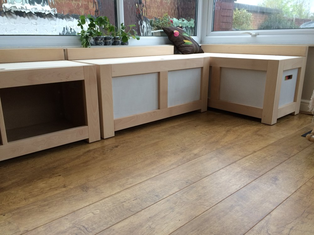 - Made from birch plywood and solid beech, these benches are very durable. This image shows the white panels are primed and ready to be painted in colours to suit the clients taste. The concealed storage is accessible through hinged seats.