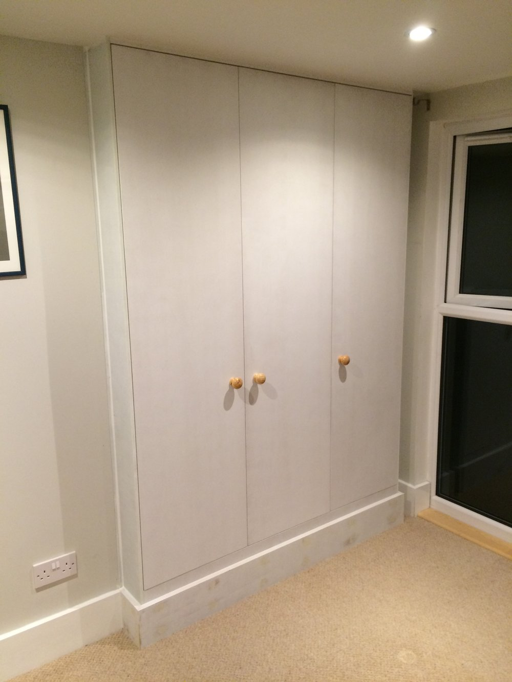 - These simple wardrobes were installed in to a fairly tight space within a loft conversion. Steel work beneath had to be hidden whilst also allowing a space for the curtains. The interiors are melamine faced, with the doors and trim being primed and ready for my client to decorate.