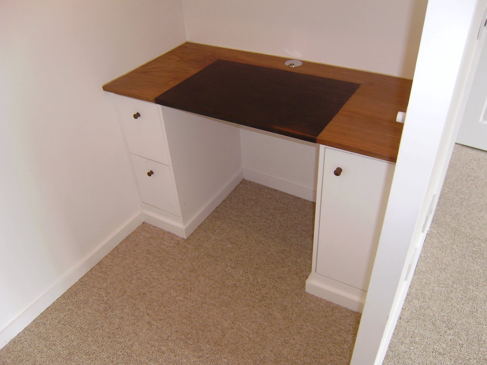 - This simple desk fills a small space off of a living room. The top is made from Walnut with a leather writing surface.