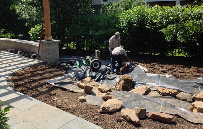Work begins on a pondless stream featuring 3 small waterfalls built of weathered boulders.