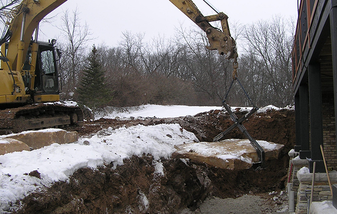 Large pieces of sandstone outcropping are set with an excavator at the base of the wall.