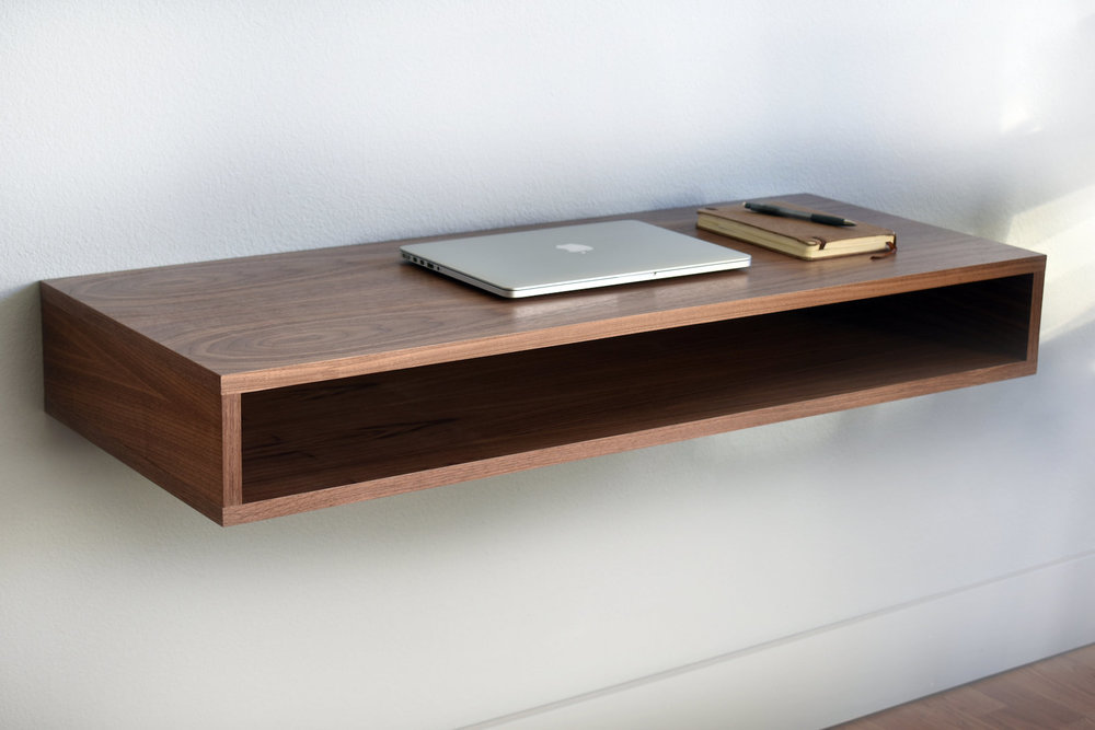 "A distinctive floating desk that adds functionality and visual appeal to any room.  Constructed of 100% wood with real walnut exterior. Unique grain pattern to each piece.  Designed to fit neatly in nearly all room layouts: Desk sized to provide space for a laptop and writing, while the compact footprint works in a bedroom, living room or office.  Integrated storage area for accessories, magazines, stationary, and writing materials.  Includes all mounting material to hang desk in 5 minutes.  Dimension: 38"" long, 16"" deep, 6"" high  Made in Seattle of 100% domestic materials"