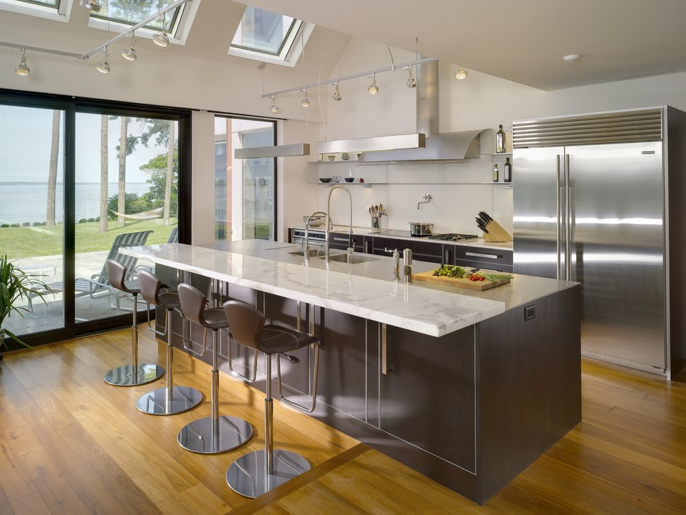 When designing this local kitchen, we opened the space to invite in natural light with a vaulted ceiling and large windows and skylights that faces the river. This view of the kitchen space shows a large island with bar height seating to accommodate guests without inviting them into the work space. Simple shelves, sleeved between the glass backsplash panels, give a clean, minimalist look to the main kitchen area. Ample storage is extended out of the initial view of the kitchen using stainless steel and frosted glass cabinetry. The black walnut finish of the island and lower cabinets anchor the kitchen while the lofty vault ceiling gives an open, airy feel.