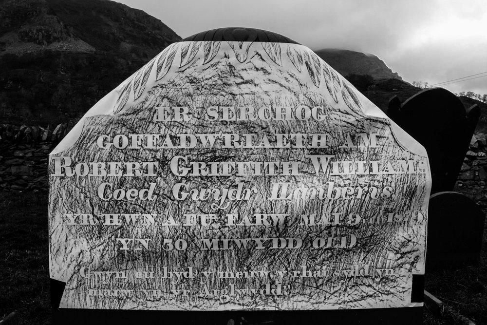 ER SERCHOG COFFADWRIAETH AM ROBERT GRIFFITH WILLIAMS Coed Gwydr Llanberis YR HWN A FU FARW MAI 9FED 1879 YN 30 MLWYDD OEDD Gwyn eu byd y meirw y rhai sydd yn marw yn yr Arglwydd IN LOVING REMEMBRANCE OF ROBERT GRIFFITH WILLIAMS Coed Gwydr Llanberis WHO DIED MAY 9TH 1879, AT 30 YEARS OLD Blessed are the dead who die in the Lord