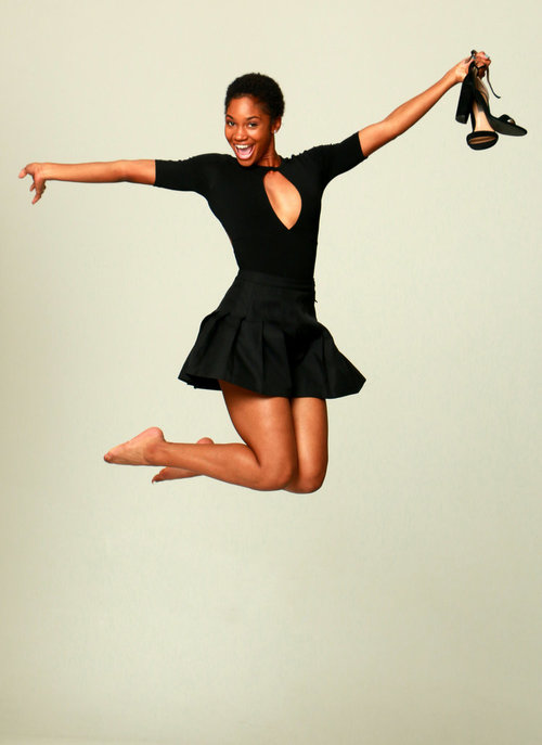 Overjoyed jumping with her shoes in hand
