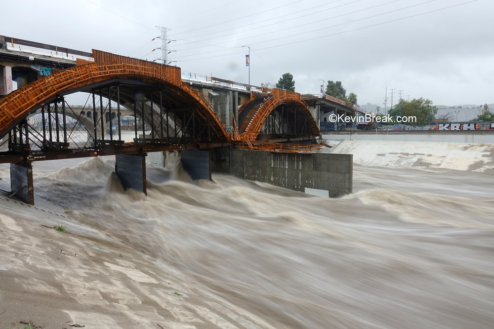Storm waters rage under Spring Street bridge