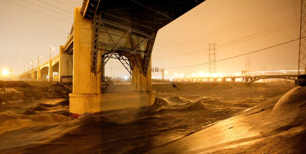 Storm waters roar under 6th Street bridge
