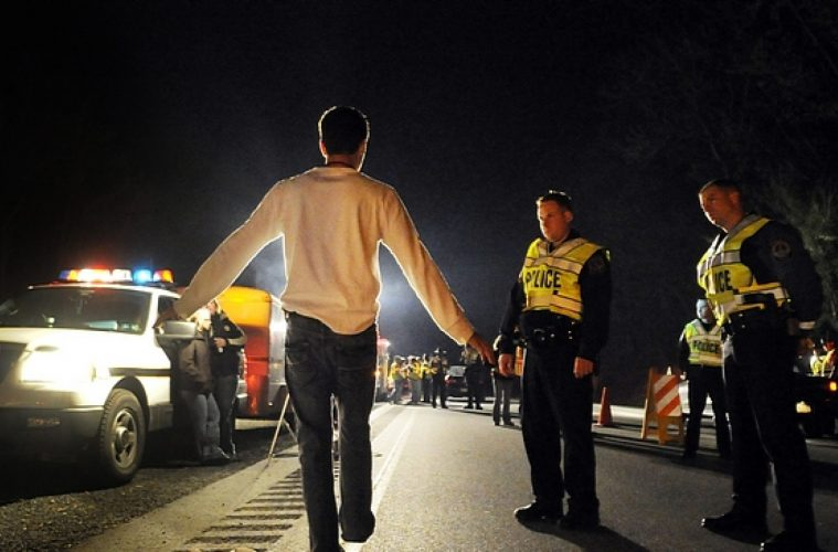 A person takes a sobriety test at a checkstop.
