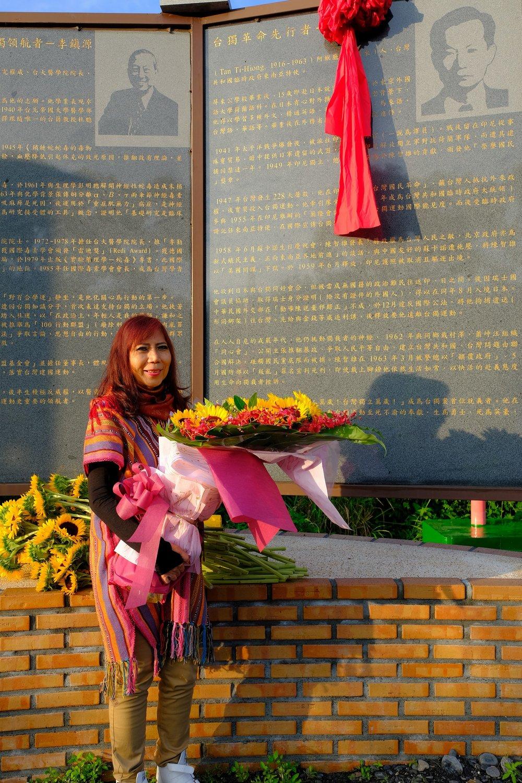 2017年5月,Vonny在聖山的「台獨革命先行者,陳智雄揭碑追思會」,獻上一大束鮮花,與父親的紀念碑合影。圖片提供:台灣大地文教基金會