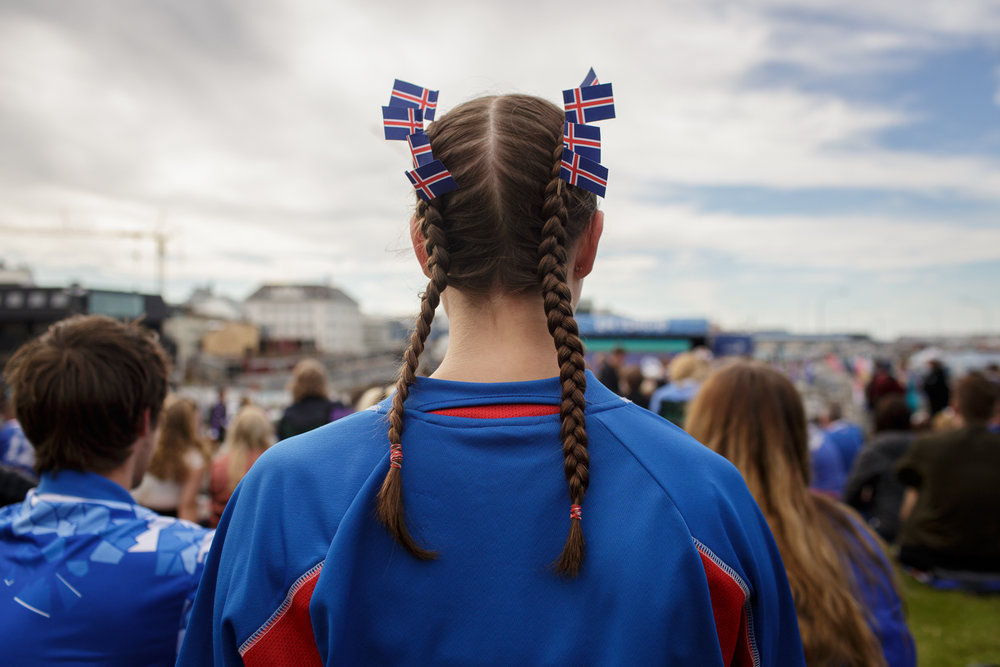 A girl wears braids adorned with Iceland's flag as she watches the Euro Cup 2016 match between Iceland and France on a big screen in downtown Reykjavik.