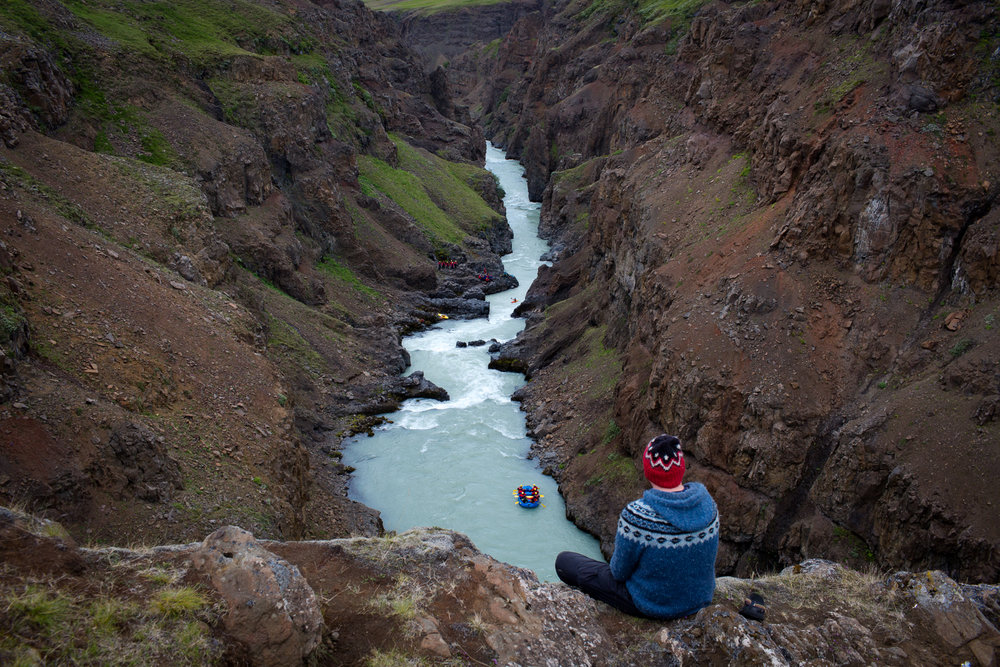 The bus driver for Viking Rafting watches a rafting group from a cliff just before they pass through a rapid on the East Glacial River.