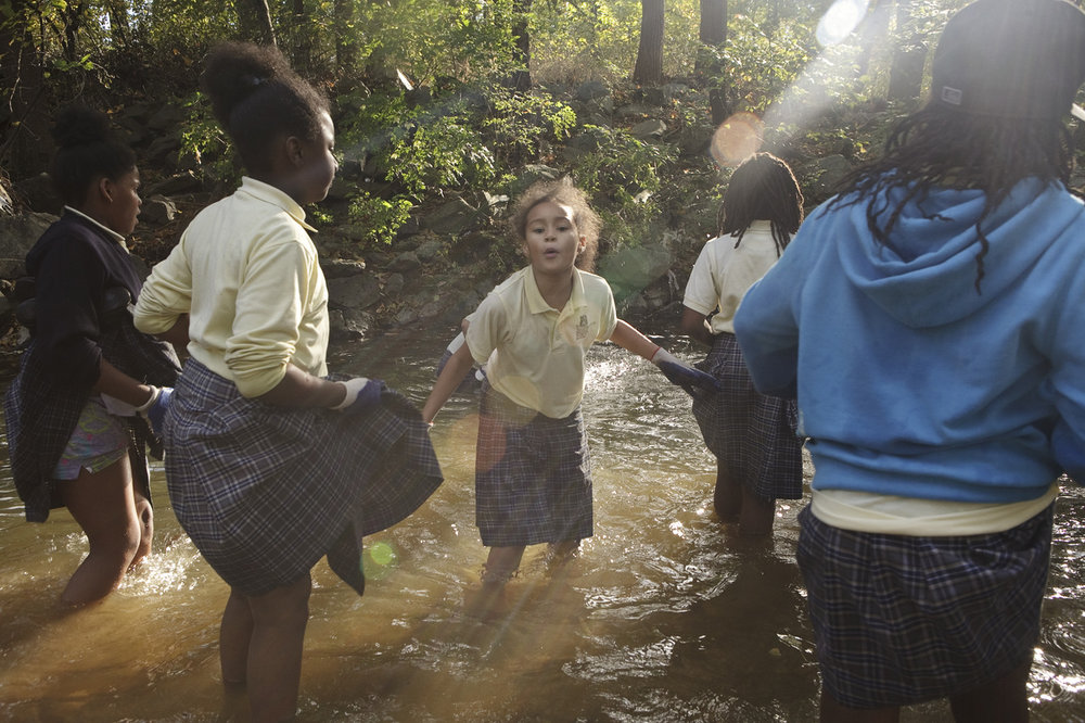 A group of girls take part in a trash clean up in a creek outside Town Hall Education Arts Recreation Campus in southeast D.C.