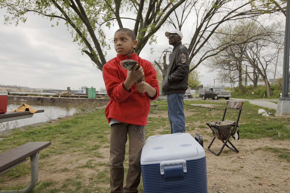Elijah holds a caught fish just south of the John Philip Sousa Bridge on a Sunday afternoon in April. He was fascinated by the fish that his dad and his friends caught.