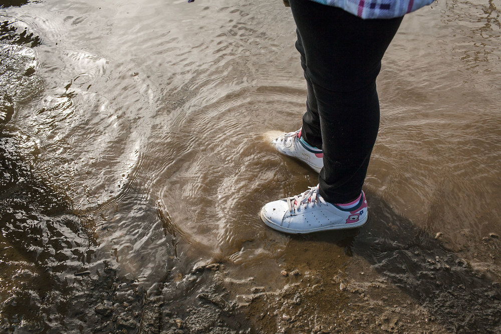 A young girl wades in the shallow water on the shore of the Anacostia River. She visited Seafarers to participate in the 2013 Earth Day Clean Up.