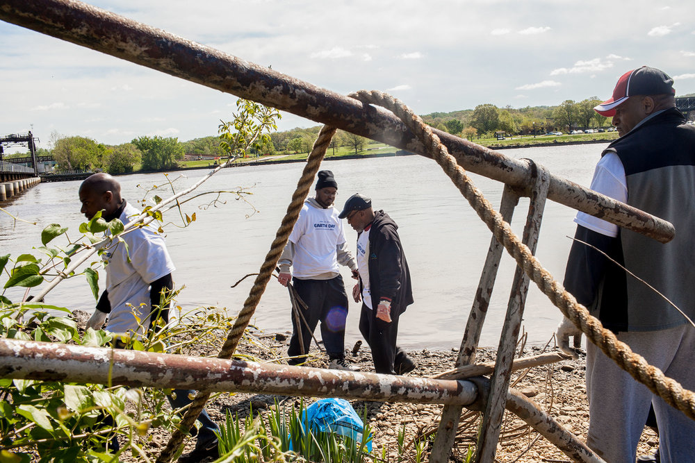 "Volunteers from the organization Concerned Black Men and their mentoring program ""Just Say Yes"" remove debris from the banks of the Anacostia River at Seafarers during the annual Earth Day clean up, now organized by the Anacostia Watershed Society, in 2013."
