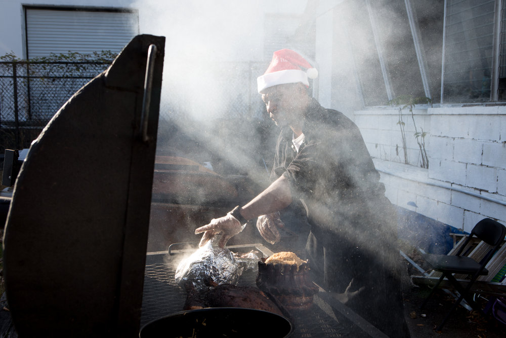 Wearing a Santa Claus hat, Maurice Marshall runs the grill at a Thanksgiving celebration in 2015.