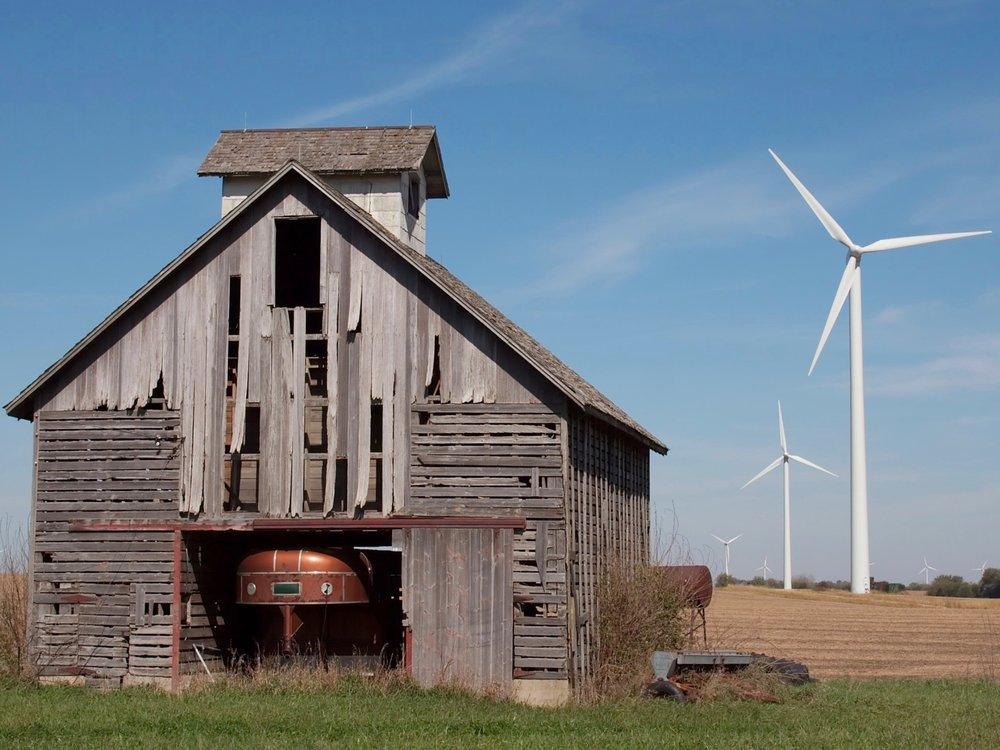 Wind turbines line up alongside an old barn in Illinois. (Wikimedia Commons/Dori)