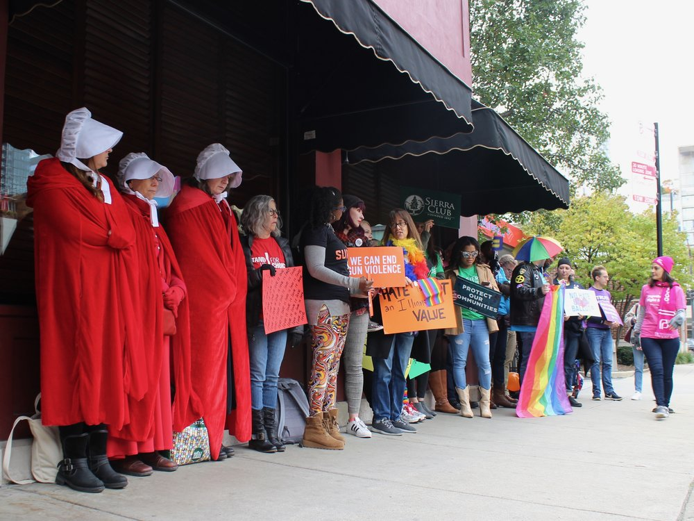 """Members of various progressive groups protested outside Erika Harold's speech in Chicago as what they described as a """"human rainbow."""" (One Illinois/Ted Cox0"""