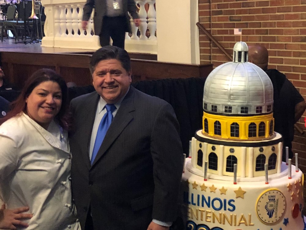 Gov.-elect Pritzker poses with the bicentennial Eli's Cheesecake before the birthday event. (One Illinois/Ted Cox)