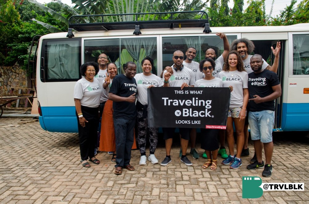 Group photo in Kumasi holding sign that says 'This is what Traveling Black looks like'. Photo credit: Kumi Rauf, Founder - Traveling Black