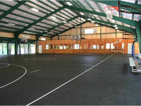 The indoor basketball facility has three courts with adjustable hoops and an electronic scoreboard.