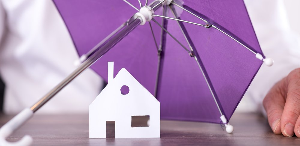 Image: White paper house being covered or protected by a purple umbrella.