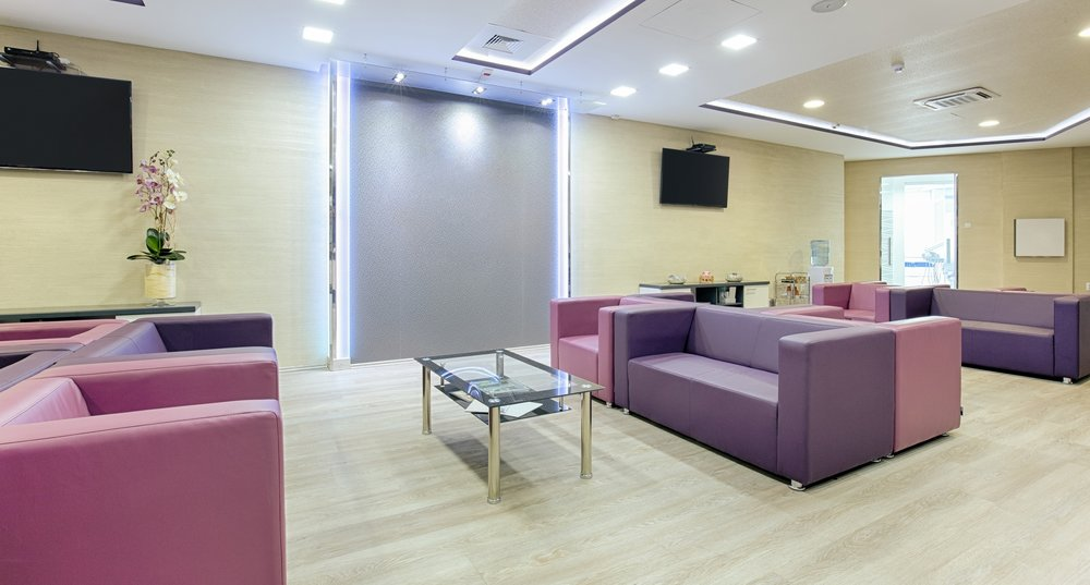 Image: A clean, relaxing empty medical waiting room with cream walls and floor and purple couches.