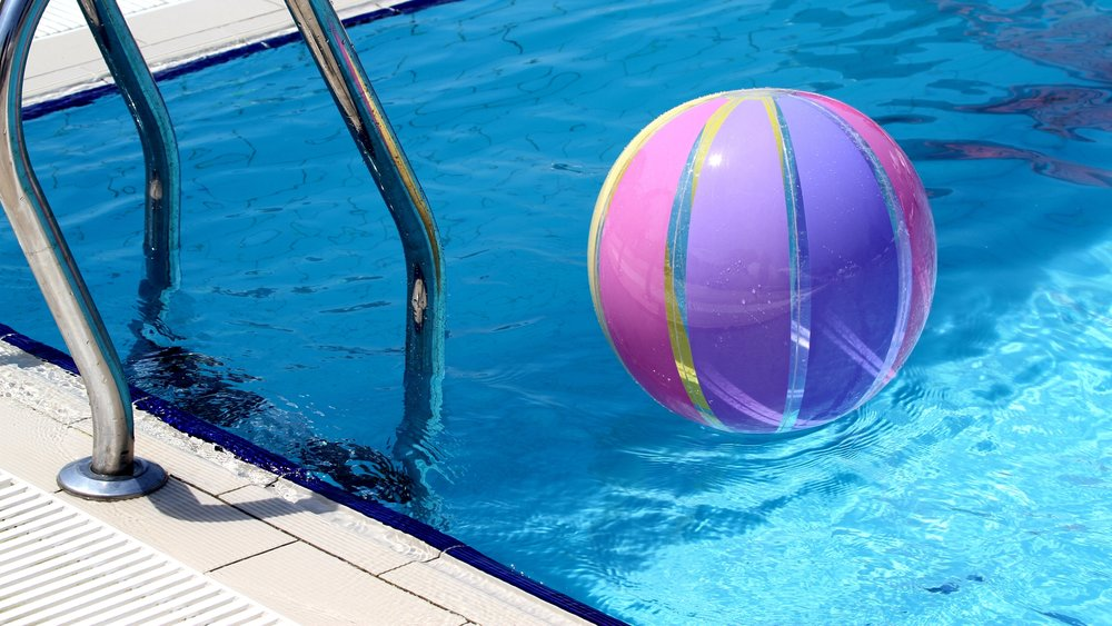Image: A purple and pink beach ball floats in a blue swimming pool.