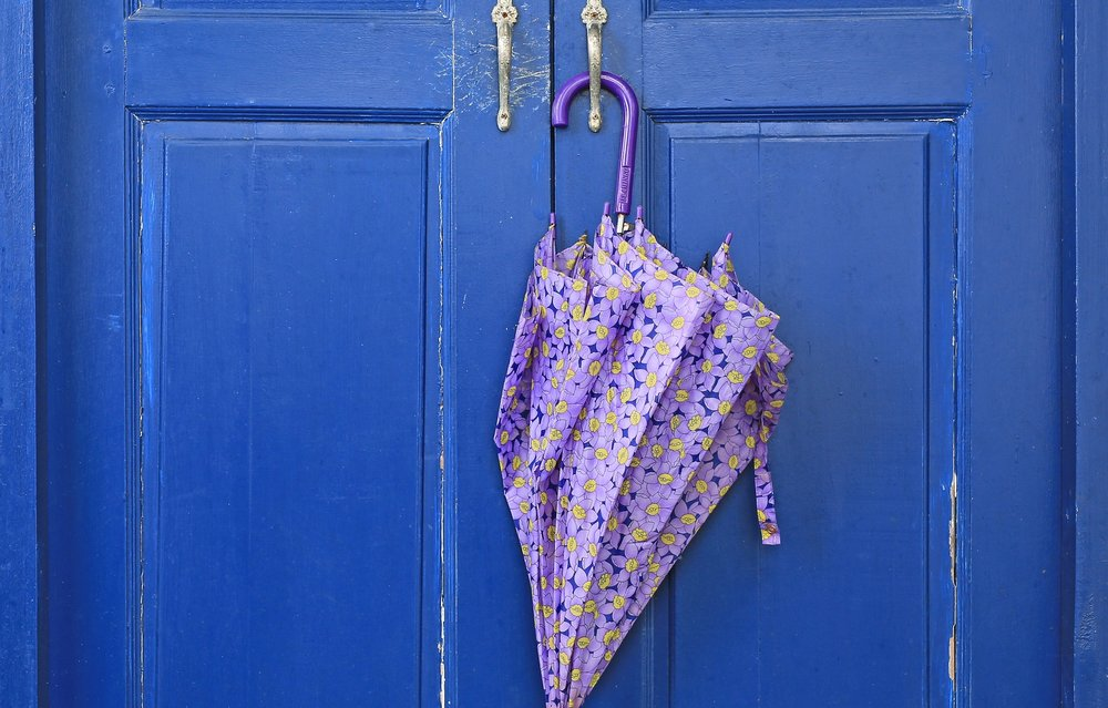 Image: A purple umbrella hangs on the handle of a worn blue door.