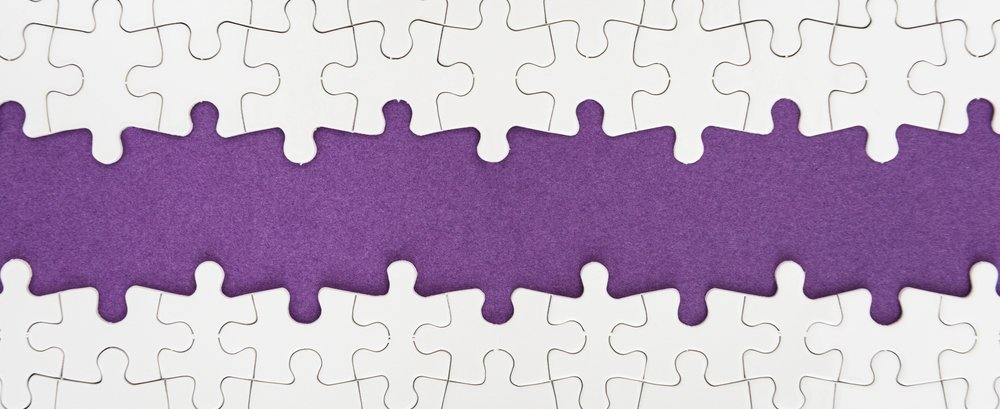 Image: White puzzle pieces missing connecting pieces in the middle. They are laying on purple felt.
