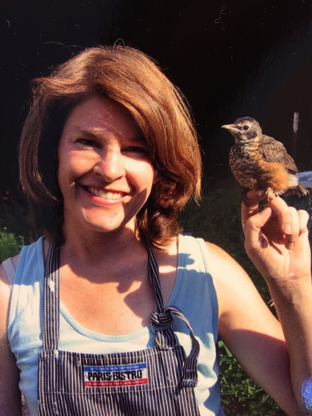 Me with Bird, a robin I raised when it fell from a nest. I taught him how to dig for worms and when you put your hand in the air, he would fly to you. It migrated about a month after this photo was taken.