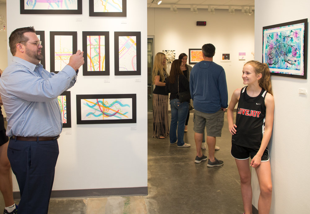 1- Ashlyn DuBois poses for her Dad in front of her watercolor art .jpg