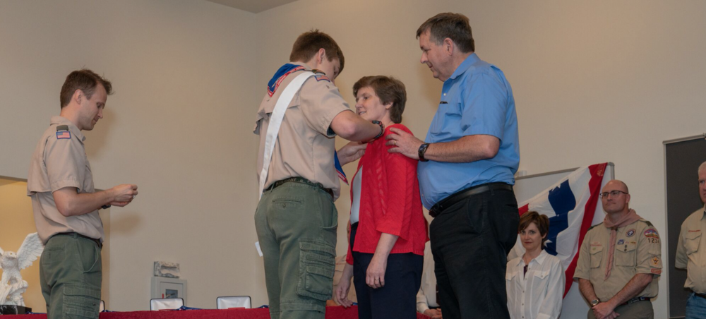 Jared Grimes affixes Eagle Scout parent pin to his mom
