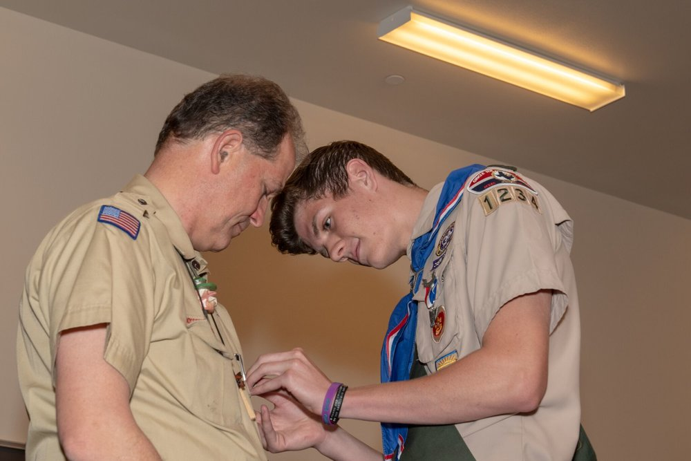 Cody Larimer pins Scoutmaster Mike Fisher with an Eagle Scout Mentor pin, one of four Fisher received during the Court of Honor ceremonies