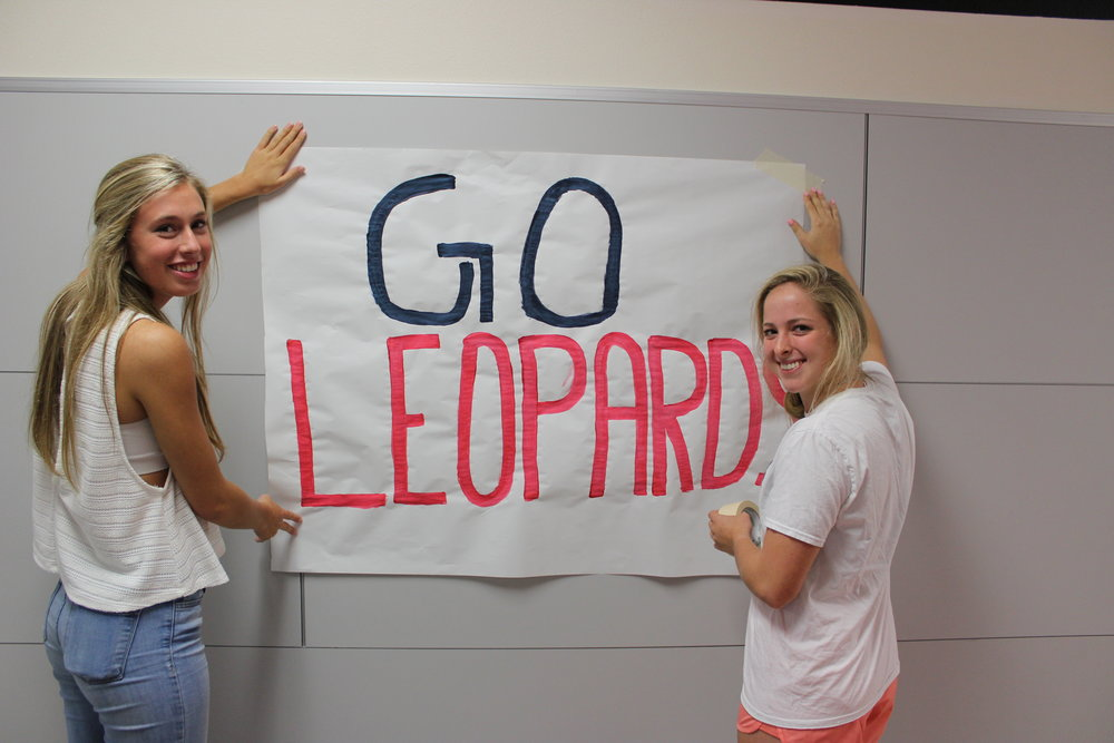 Varsity cheerleaders, (from left) Lacie Gager and Madison Kohl, decorate the school with spirit posters.