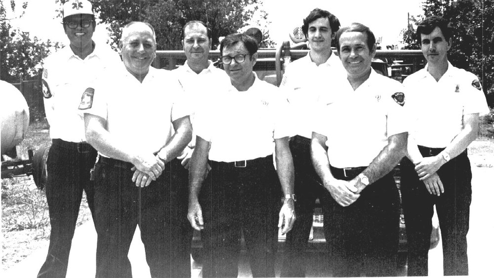 Lee Bauer (center) with Chief Frank Hamlin (left of center) and other volunteer firefighters. Photo provided by Lucas FD.