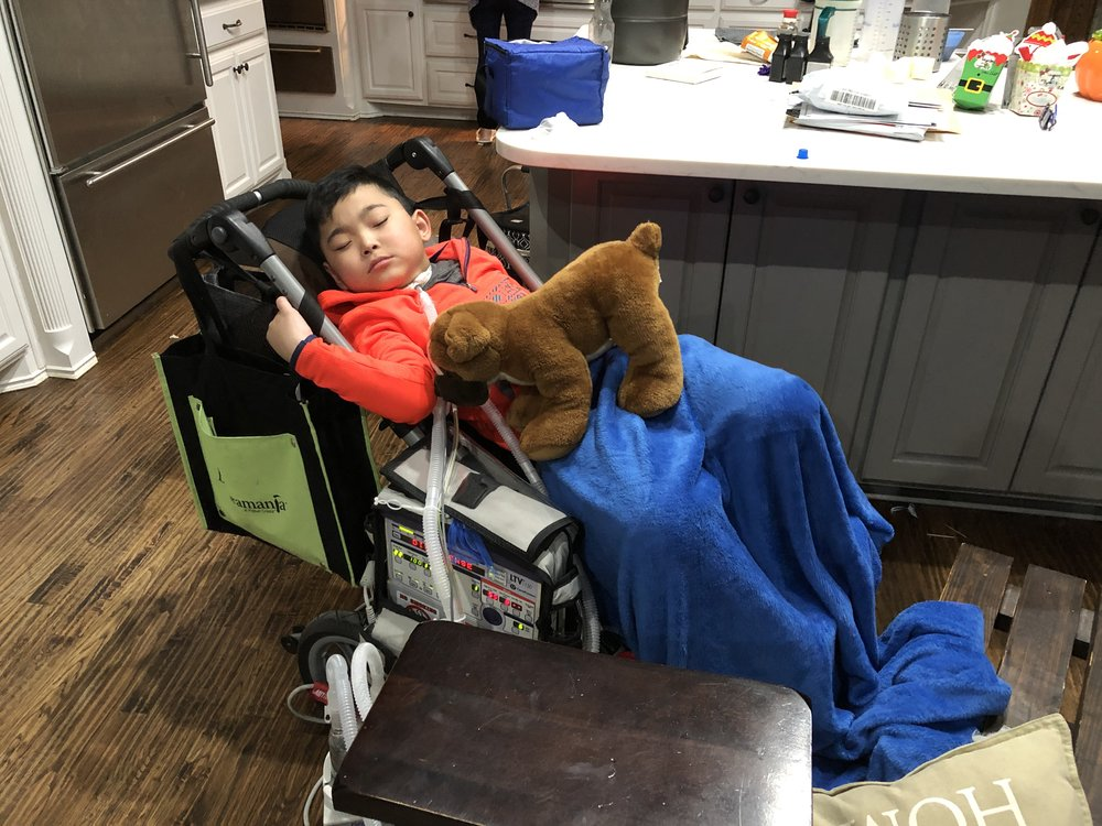 ": Laynson rests at home after a day at school. This ""stroller"" is equipped with a ventilator and other emergency equipment. Each school day it goes to school with Laynson."