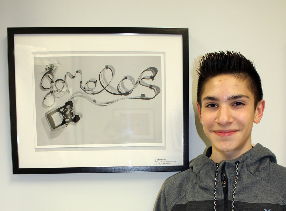 Lovejoy High School student, Luis Sandoval, next to his artwork titled 'Gemelos'.