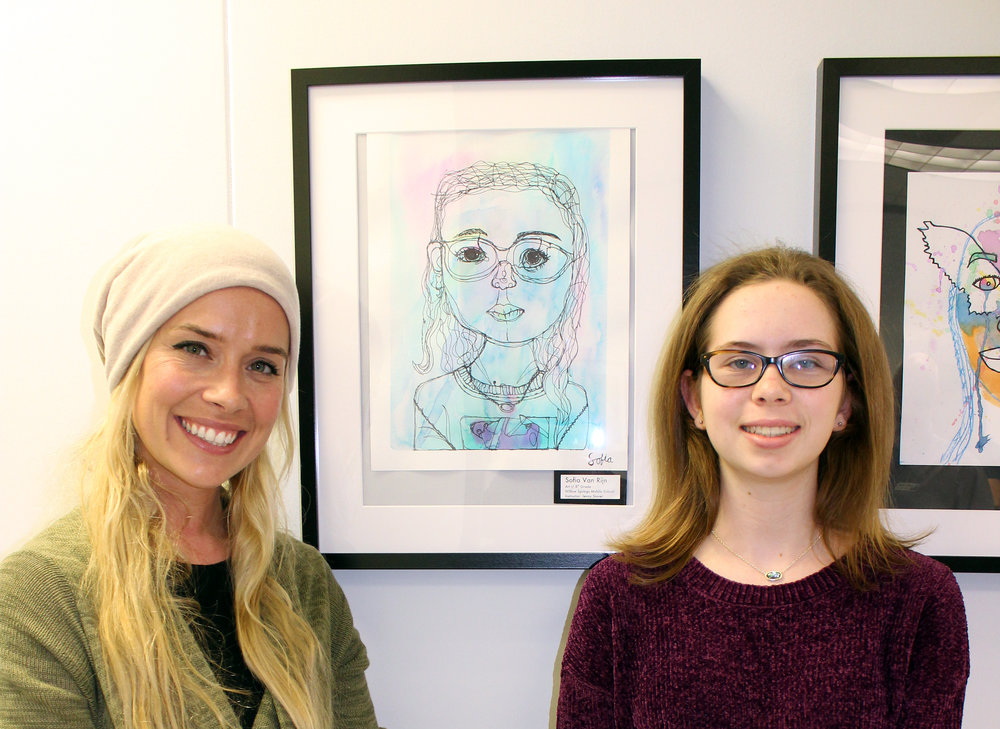 Willow Springs student, Sofia Van Rijn (right), next to her self-portrait. Pictured with her is her art teacher, Jenny Slaver (left).